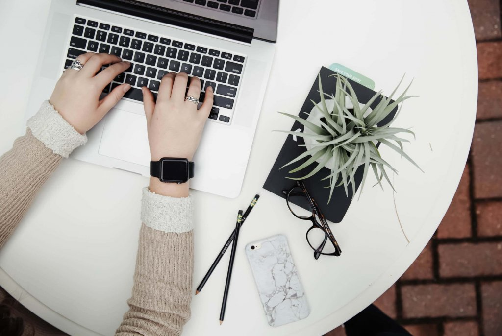 social media manager - hands with apple watch glasses and laptop on a table