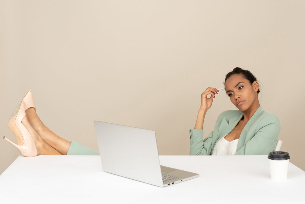 content marketing mistakes - woman in green thinking and working on a laptop with a coffee on the table
