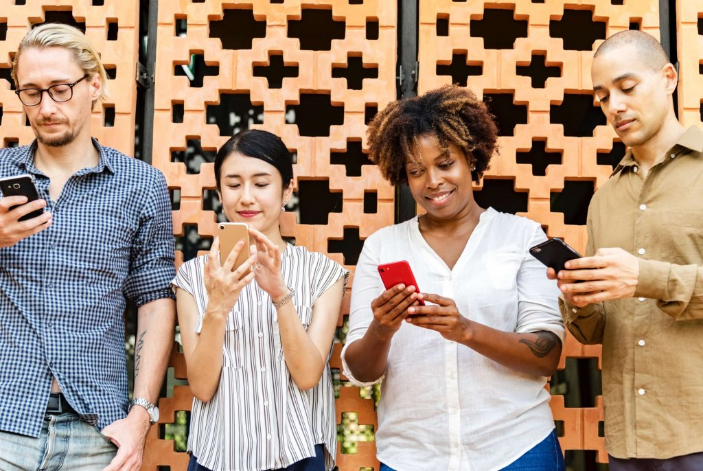 ultimate list of marketing communities - two men and two women with phones in their hands