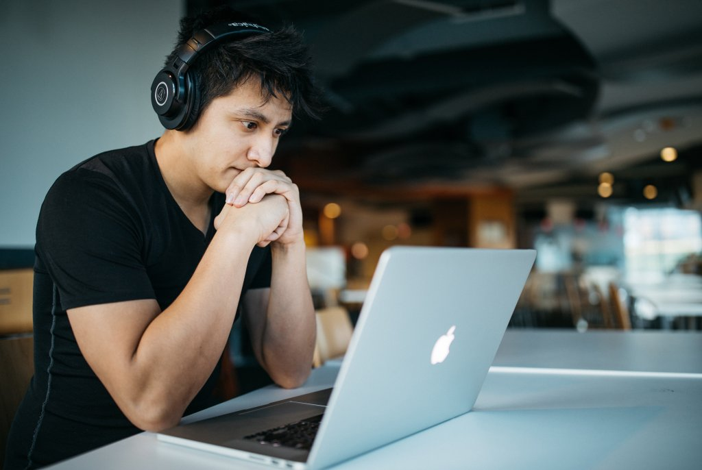 content marketing mistakes - man working on a laptop with headphones