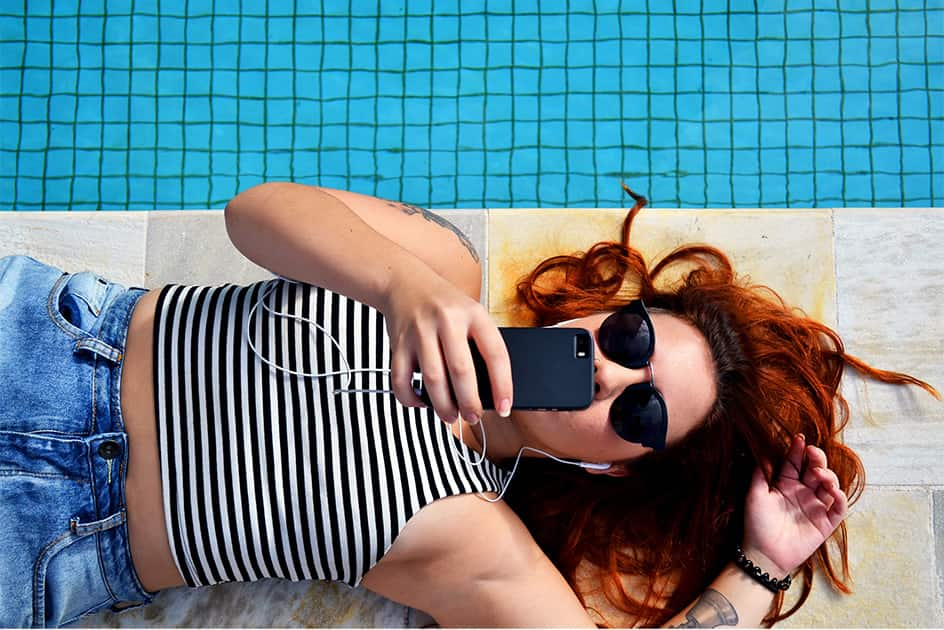 IGTV and Instagram Stories for Lead Generation redhead girl laying next to the swimming pool dressed in jeans and strippes with mobile phone and headphones