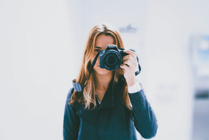 engaging videos for social media woman taking a picture with a canon camera